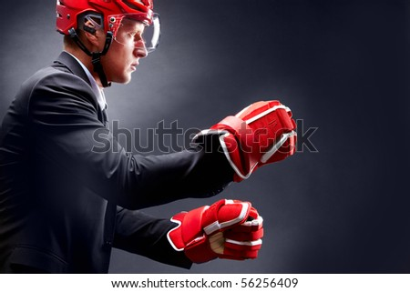 Portrait of young businessman in suit and hockey helmet and gloves fighting - stock photo