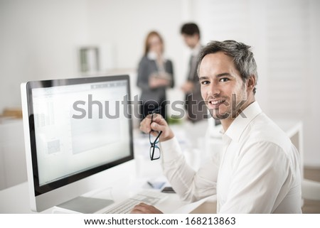 portrait of young businessman in workplace - stock photo