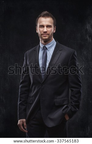 Portrait of young businessman isolated over dark background - stock photo
