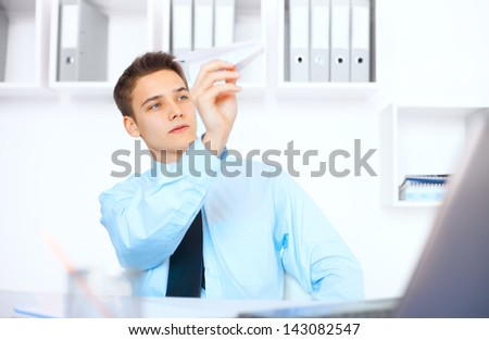 Portrait of young businessman launch a paper airplane at his workplace in bright office - stock photo