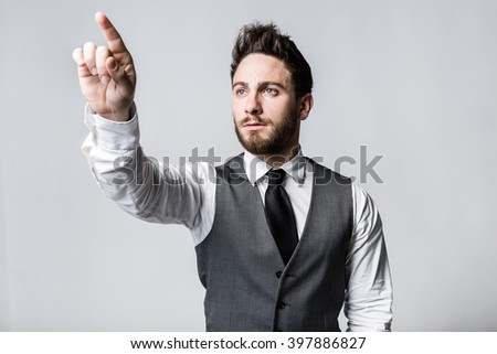 Portrait of young businessman pressing a button on an imaginary screen. - stock photo