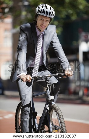 Portrait of young businessman riding bicycle - stock photo
