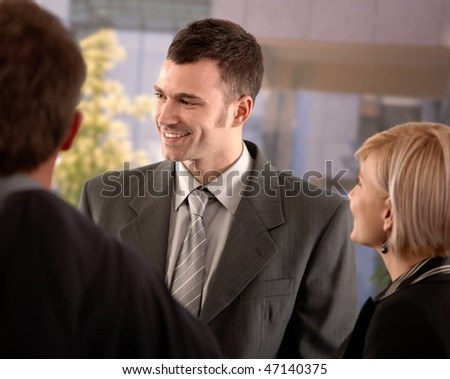 Portrait of young businessman standing outdoor talking with colleagues, smiling. - stock photo
