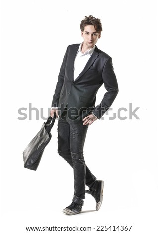 Portrait of young businessman standing with his bag walking in studio - stock photo