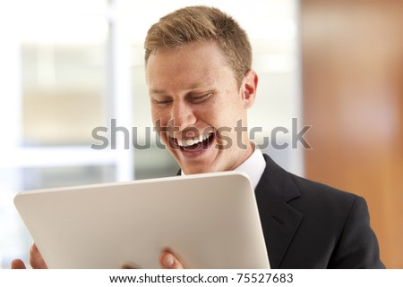 Portrait of young businessman standing with touch screen computer - stock photo