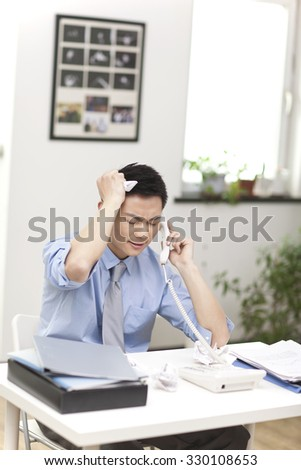 Portrait of young businessman talking on phone in office - stock photo