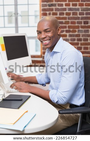 Portrait of young businessman using computer in the office - stock photo
