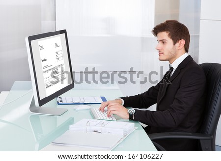 Portrait Of Young Businessman Using On Computer At Desk - stock photo