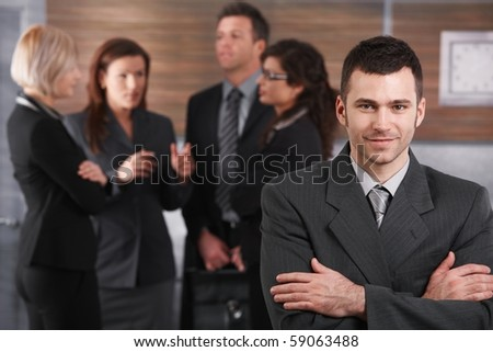 Portrait of young businessman wearing grey suit, standing with arms crossed in office.? - stock photo