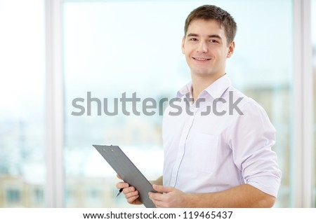 Portrait of young businessman with clipboard looking at camera - stock photo