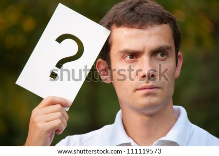 Portrait of young businessman with question mark - stock photo