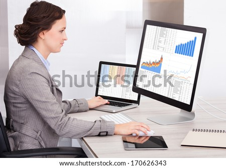 Portrait Of Young Businesswoman Analyzing Graph On Computer - stock photo