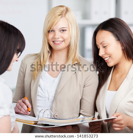 Portrait of young businesswoman holding binder with female coworkers looking at it in office - stock photo