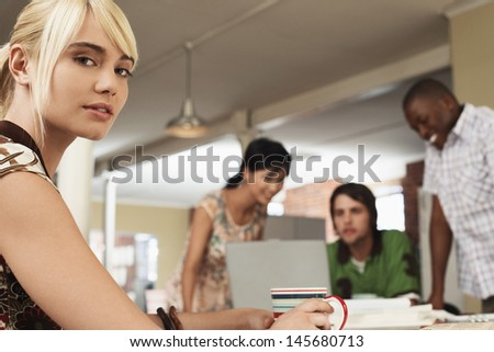 Portrait of young businesswoman holding coffee cup with colleagues using laptop in background - stock photo