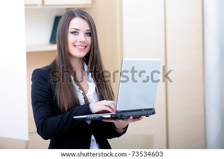 Portrait of young businesswoman holding laptop and smiling to you - stock photo