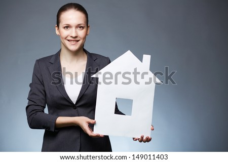 Portrait of young businesswoman holding paper house and looking at camera - stock photo