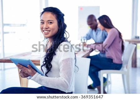 Portrait of young businesswoman holding tablet PC with colleagues in background at creative office - stock photo