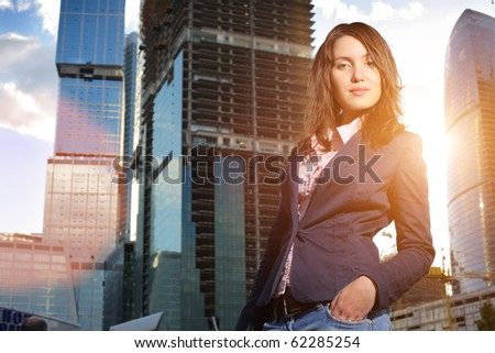 Portrait of young businesswoman in front of construction site at sunset. - stock photo