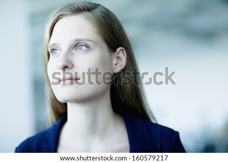 Portrait of young businesswoman looking away in contemplation - stock photo