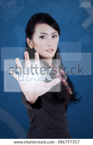 Portrait of young businesswoman pushing tax button on the virtual screen - stock photo