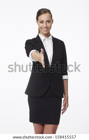 Portrait of young businesswoman shaking hands - stock photo