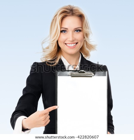 Portrait of young businesswoman showing blank clipboard, with copyspace area for text or slogan, on blue background - stock photo