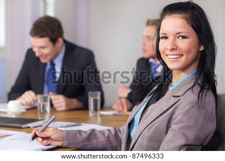 Portrait of young businesswoman sitting at conference table during business meeting - stock photo