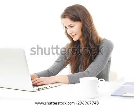 Portrait of young businesswoman sitting in front of laptop and typing on keyboard. Isolated on white background. - stock photo