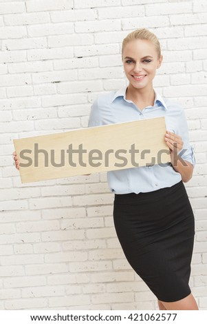 portrait of young businesswoman smiling while holding blank board - stock photo