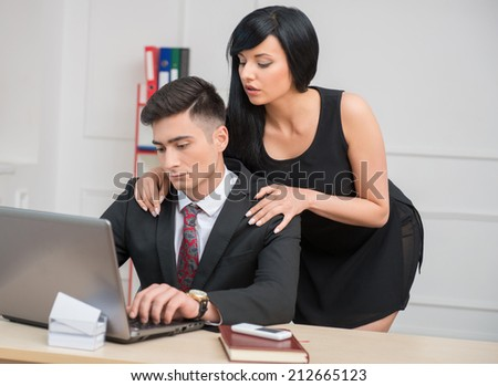 Portrait of young businesswoman standing behind  her working on computer and tired  colleague and flirting with him in office, relationship at work concept, copy space on the wall - stock photo