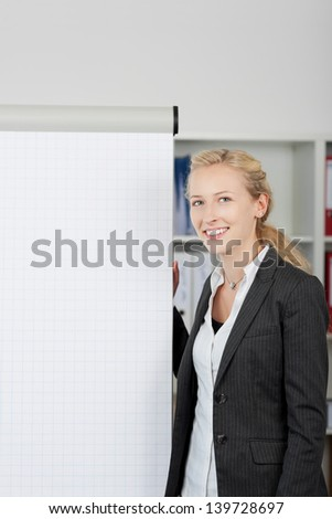 Portrait of young businesswoman standing by flipchart in office - stock photo