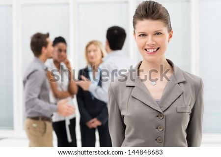 Portrait Of Young Businesswoman Standing In Front Of Co-workers at Office - stock photo