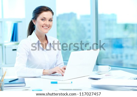 Portrait of young businesswoman typing on laptop - stock photo