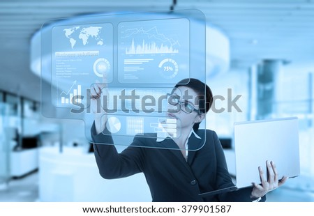 Portrait of young businesswoman using a virtual screen to make financial statistics while holding laptop in the office - stock photo