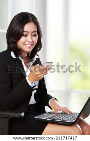 portrait of young businesswoman using mobile phone while working in the office - stock photo