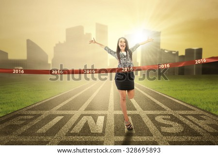 Portrait of young businesswoman winning the competition and crossing the finish line with numbers 2016 - stock photo