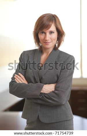 Portrait of young businesswoman with arms crossed - stock photo