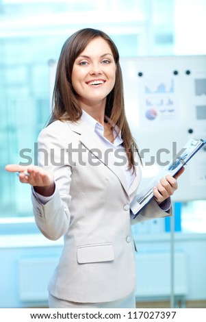 Portrait of young businesswoman with clipboard looking at camera in office - stock photo