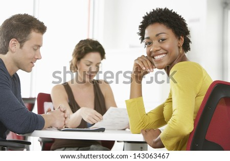 Portrait of young businesswoman with colleagues in meeting room - stock photo