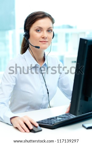 Portrait of young businesswoman with headset typing on computer keyboard - stock photo