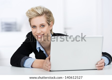 Portrait of young businesswoman with laptop at desk - stock photo
