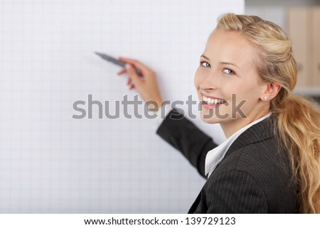 Portrait of young businesswoman writing at flip chart in office - stock photo