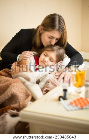 Portrait of young caring mother kissing in head sick daughter in bed - stock photo