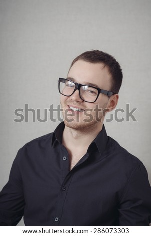 Portrait of young casual man with glasses smiling - stock photo