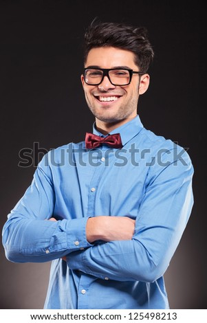 Portrait of young casual man with glasses smiling on dark background - stock photo