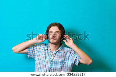 Portrait of young casual man with headphones on head. Studio shot  - stock photo
