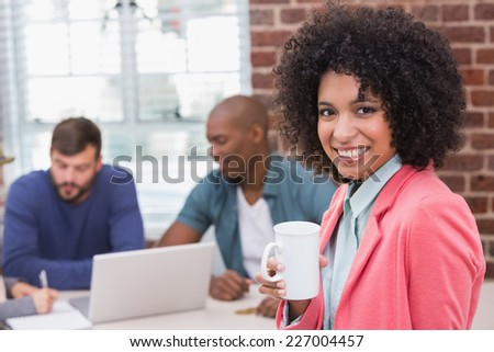 Portrait of young casual woman with colleagues behind in the office - stock photo