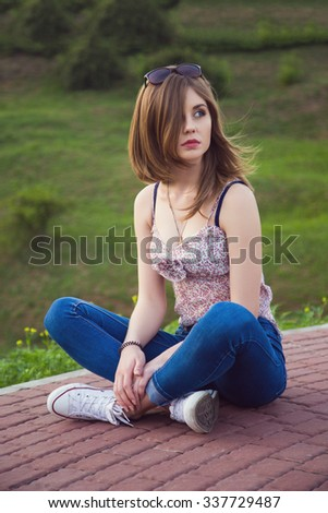 Portrait of young caucasian beautiful girl in jeans and gumshoes. Outdoors. - stock photo