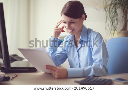 Portrait of young caucasian business woman in blue shirt at her office reading the documents. - stock photo
