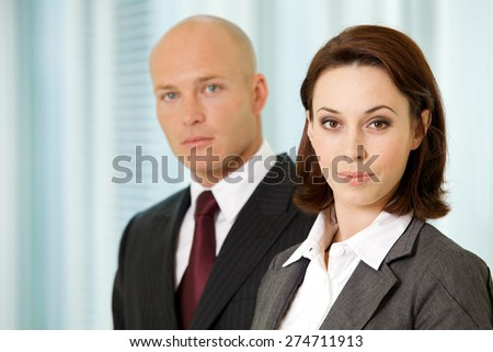 Portrait of young caucasian businessman and businesswoman in office - stock photo